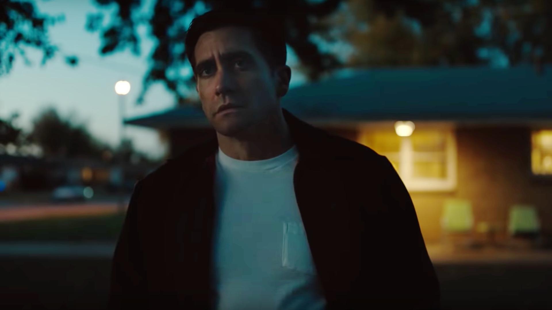Jake Gyllenhaal, devant sa maison dans le clair-obscur ; il a l'air triste.